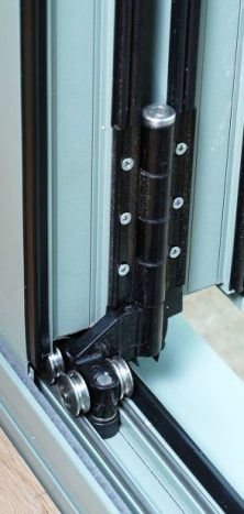 An image showing a close up of stainless steel rollers on a bifolding door