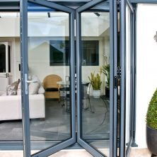 An image of bifold glass patio doors on a modern house