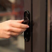 An image showing a hand turning a black handle on a bifolding door to open it.