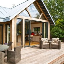 An image showing the exterior of a home with bifolding doors leading onto decking in Harrow.