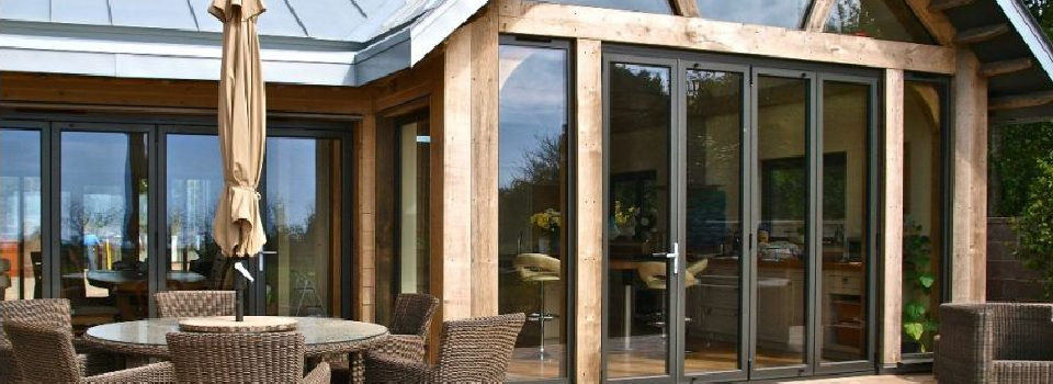 An image showing a new build property with bifolding doors in a traditional wooden structure.