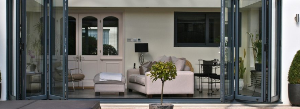 An image showing an interior view of a living room showing a cream leather sofa through a set of bifolding doors.