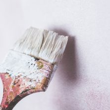 An image of someone renovating a home, painting a white wall with a paint brush.